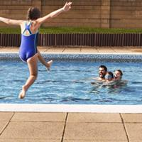 Child jumping into the pool with family